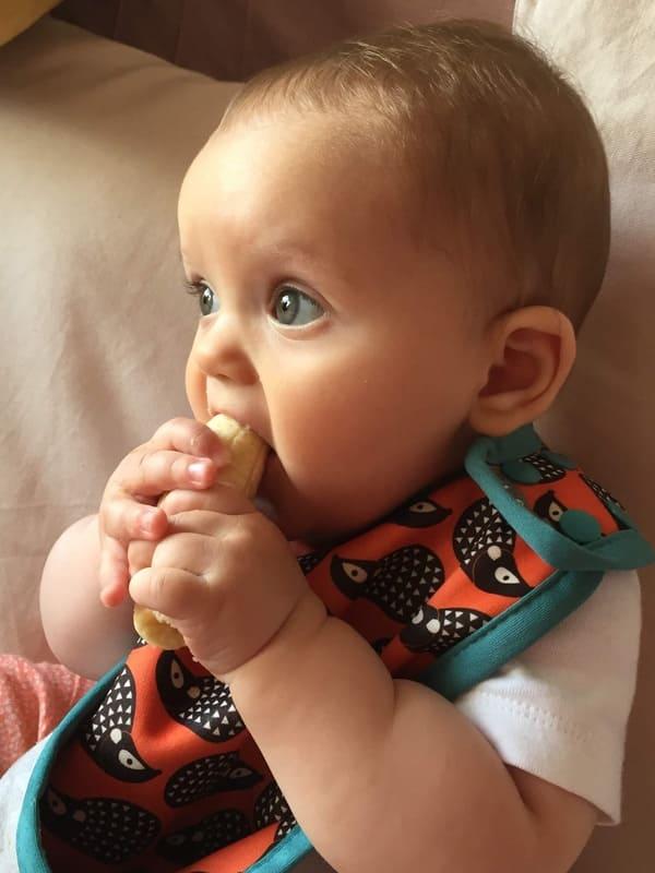 Niña de 7 meses comiendo un plátano con sus manos