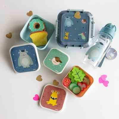 Botella, fiambrera y cajas de almuerzo de diferentes colores y diseños de divertidos monstruitos